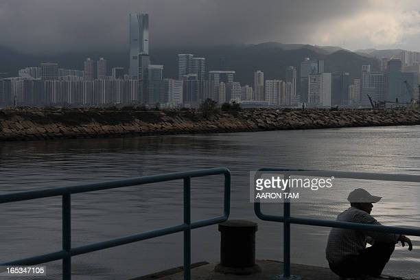 A man squats at a ferry dock overlooking Hong Kong's Victoria Harbour on March 6 2012 Hong Kong and Shanghai markets fell for a second straight day...