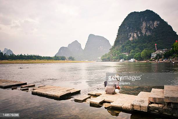 man squatting by li river. - merten snijders stock pictures, royalty-free photos & images