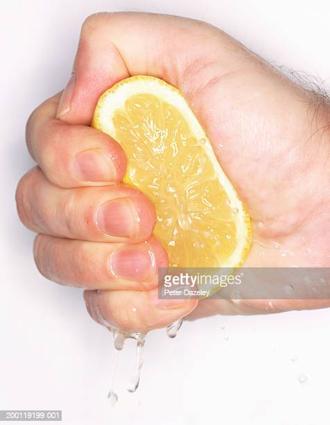 Man squeezing cut lemon in fist, close-up