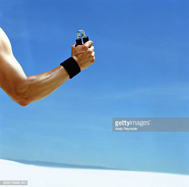 Man squeezing hand strengthener on sand dune, close-up of arm
