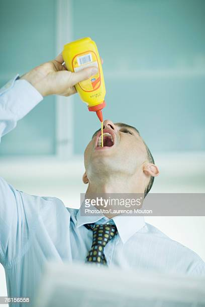 Man squeezing mustard into mouth