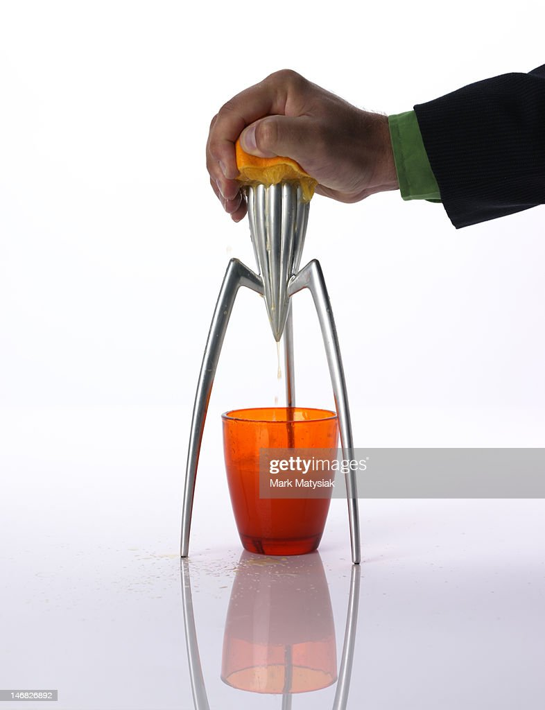Man squeezing orange juice with retro juicer : Bildbanksbilder