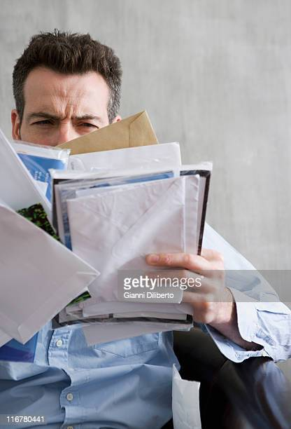 A man squinting at a bunch of mail he's holding