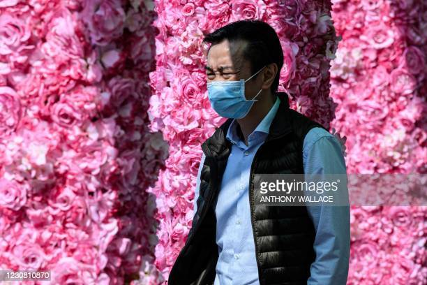 Man squints in the bright sunlight as he walks through a floral themed passageway in Hong Kong on January 27, 2021.