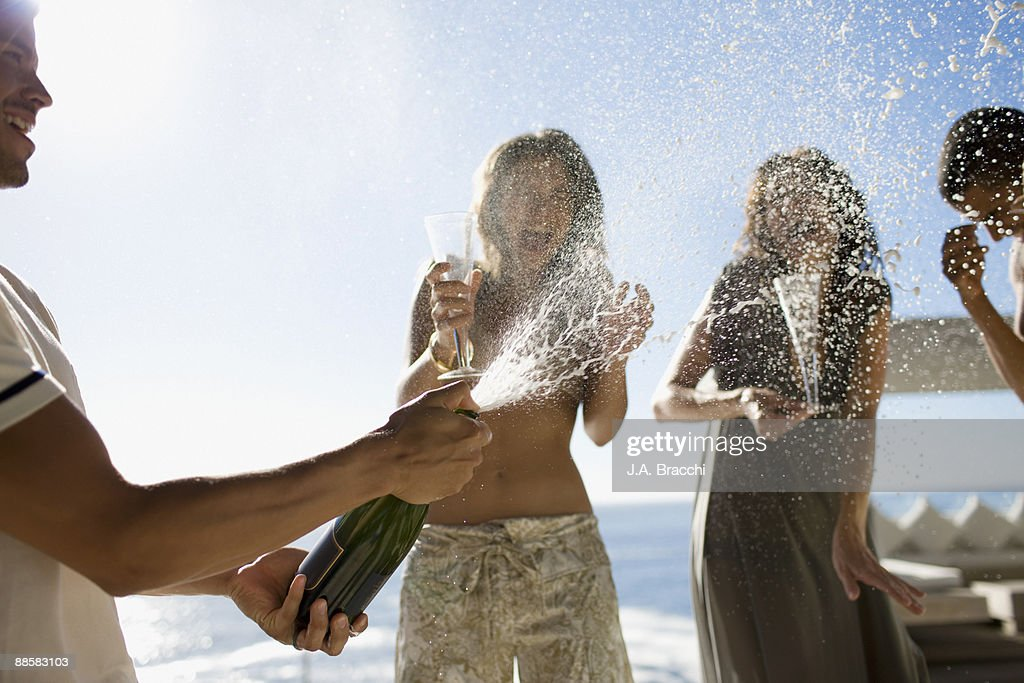 Man squirting friends with champagne : Stock Photo
