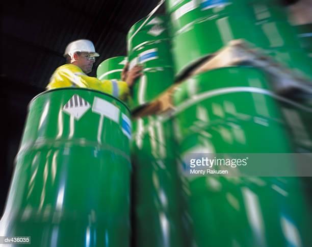 Man stacking metal barrels