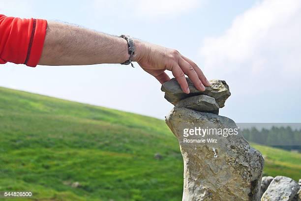 man stacking stones in perfect balance - トレイル表示 ストックフォトと画像