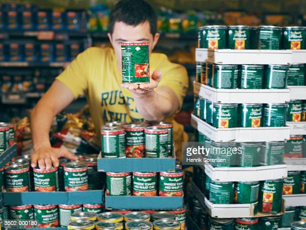 man stacking tomato sauce cans - 積み重ねる ストックフォトと画像