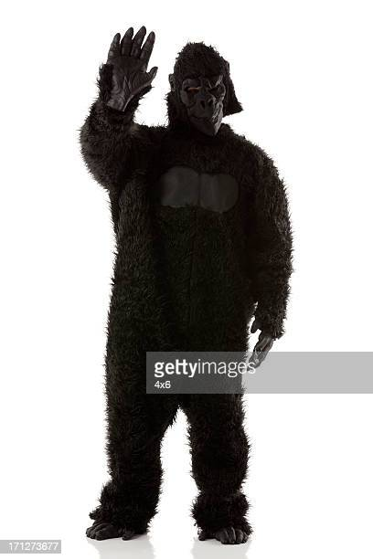 man stading in gorilla costume waving his hand - gorilla hand stock photos and pictures