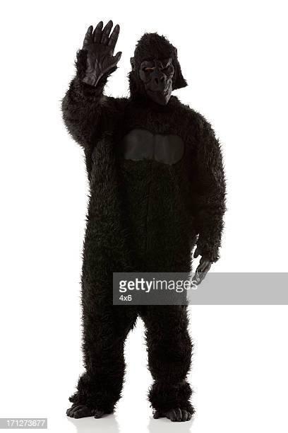 Homme en costume de gorille stading agitant sa main