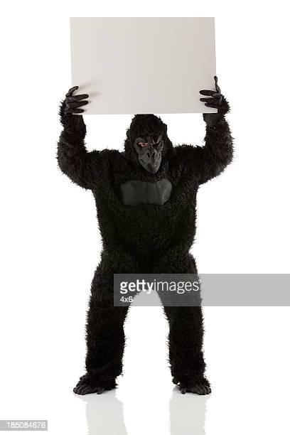 Mann stading in gorilla Kostüm mit einem Schild am Flugsteig