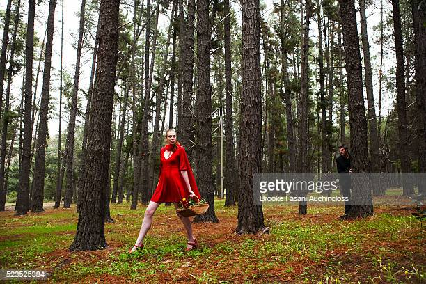 Man stalking adult little red riding hood in forest