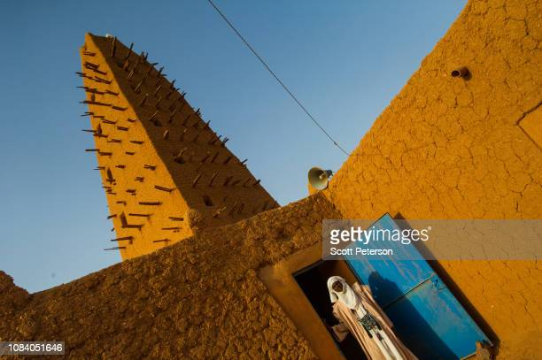Man stand in the door of a 16th-century mosque, in front of the tallest minaret made of mud in the world, as Nigeriens struggle to cope with the...