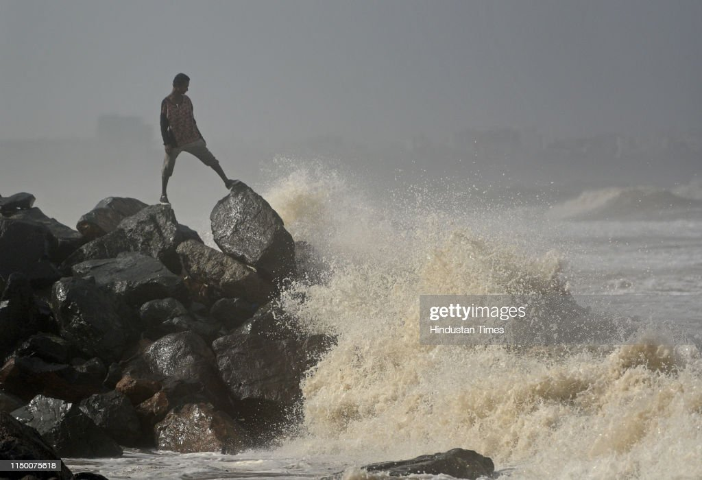 A man stand on rock on the seashore while high tide at