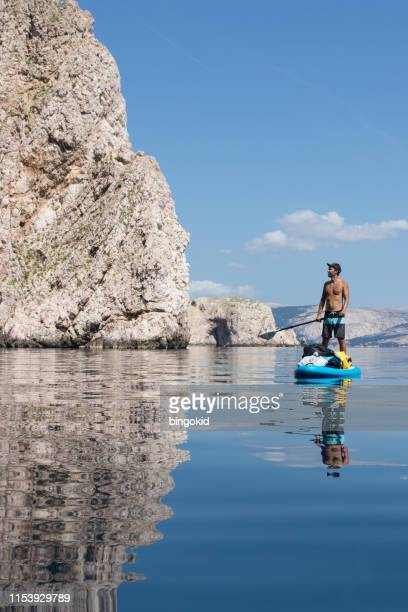 man stand up paddling under the cliffs - paddling stock pictures, royalty-free photos & images