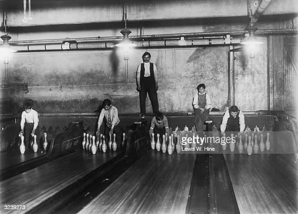 A man standing above four bowling lanes as pin boys set up pins at a bowling alley located in the New York subways