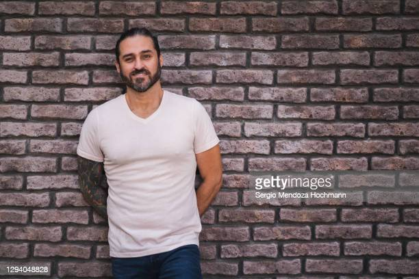 man standing against a grey and purple brick wall looking at the camera - white t shirt stock pictures, royalty-free photos & images