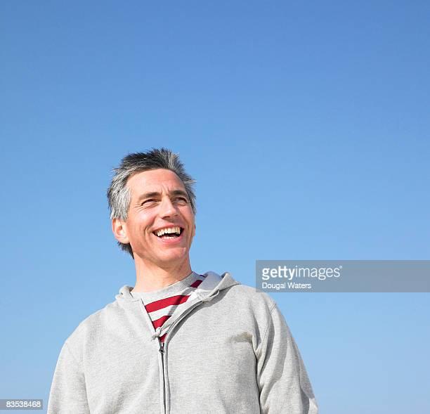 Man standing against blue sky.