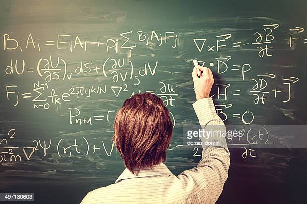 man standing against chalkboard, solves physics equations, rear view, retro - physics stock pictures, royalty-free photos & images