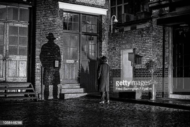 man standing against closed door of house - film noir style stock pictures, royalty-free photos & images
