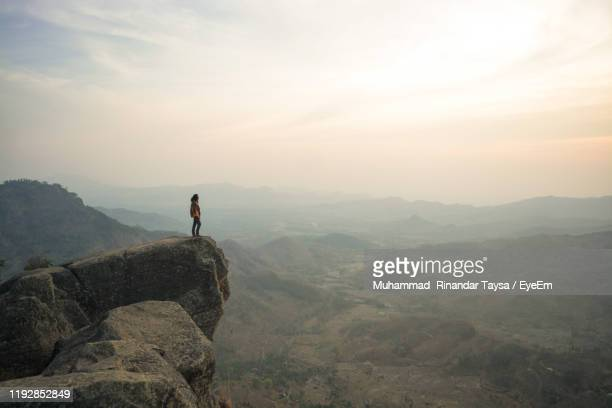 man standing against mountains on cliff during sunset - at the edge of stock pictures, royalty-free photos & images