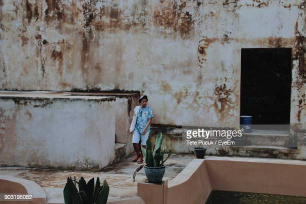 Man Standing Against Old Building
