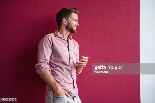 man standing against purple wall holding cell phone - nur erwachsene stock-fotos und bilder
