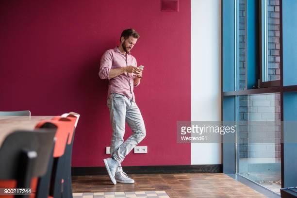 man standing against purple wall holding cell phone - lehnend stock-fotos und bilder