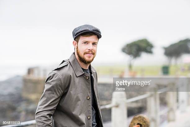 man standing against railing at seaside - flat cap stock pictures, royalty-free photos & images