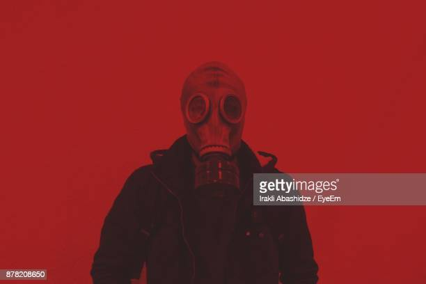 man standing against red background - gas mask stock pictures, royalty-free photos & images