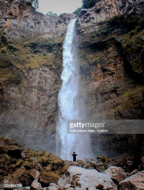 Man Standing Against Waterfall