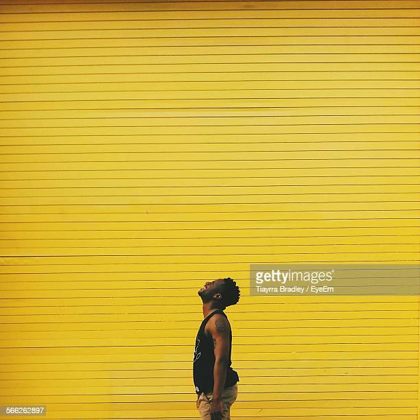 Man Standing Against Yellow Shutter