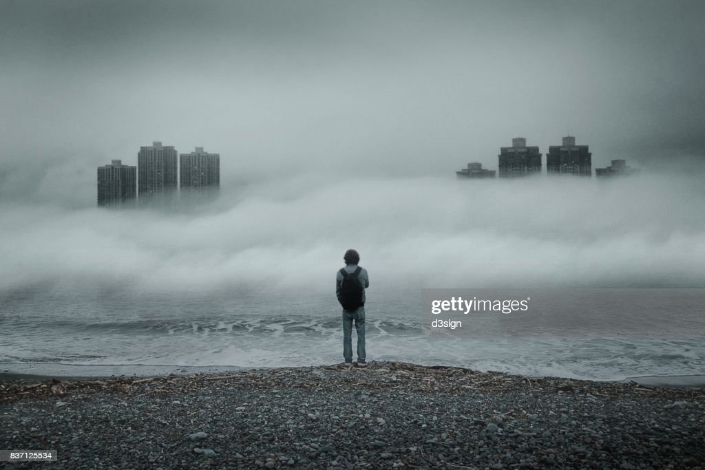 Man standing alone looking out to sea against moody sky during foggy weather : Stock Photo