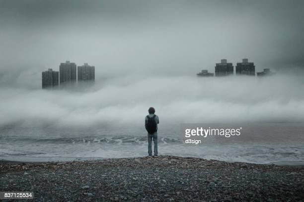 man standing alone looking out to sea against moody sky during foggy weather - fog stock photos and pictures