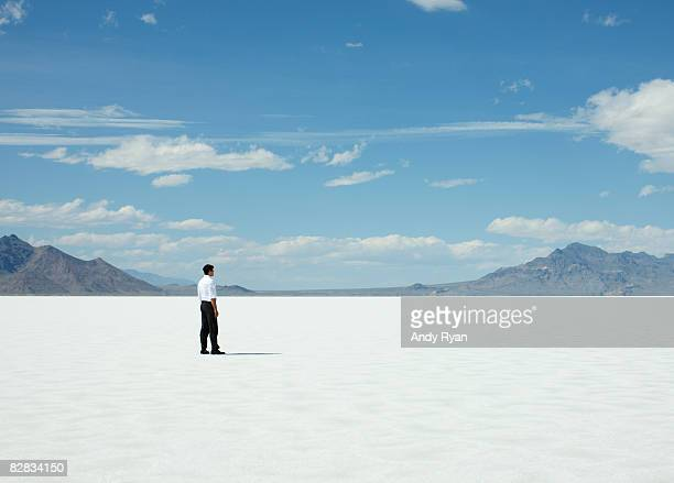 man standing alone on salt flats. - remote location stock pictures, royalty-free photos & images