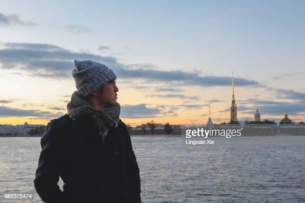 man standing along the neva river at dusk, st. petersburg - russische kultur stock-fotos und bilder
