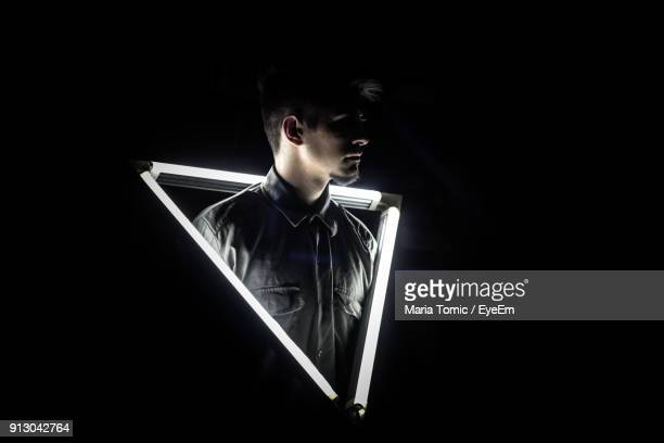Man Standing Amidst Illuminated Lights Black Background