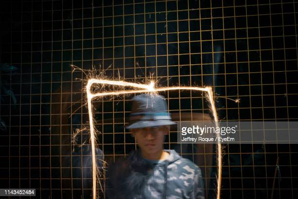 man standing amidst light painting against fence - jeffrey roque stock photos and pictures
