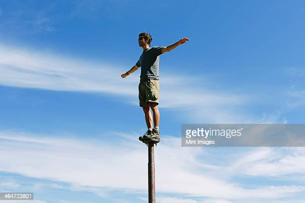 Man standing and balancing on a metal post,looking towards expansive sky,on Surprise Mountain,Alpine Lakes Wilderness,Mt. Baker-Snoqualmie National forest.