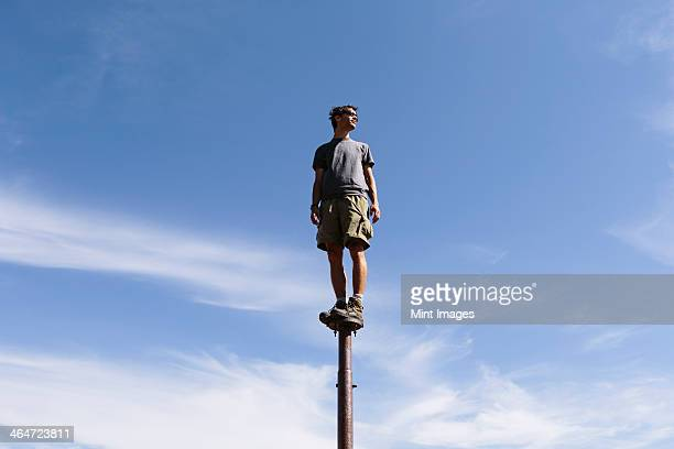 Man standing and balancing on a metal post,looking towards expansive sky,Surprise Mountain,Alpine Lakes Wilderness,Mt. Baker-Snoqualmie National forest.