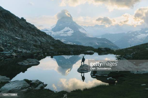 man standing and  looking at scenic view of lake near matterhorn mountain - reflection lake stock photos and pictures