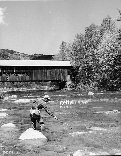 Man standing ankle deep and fishing in the Swift River, Albann, New Hampshire, circa 1950.