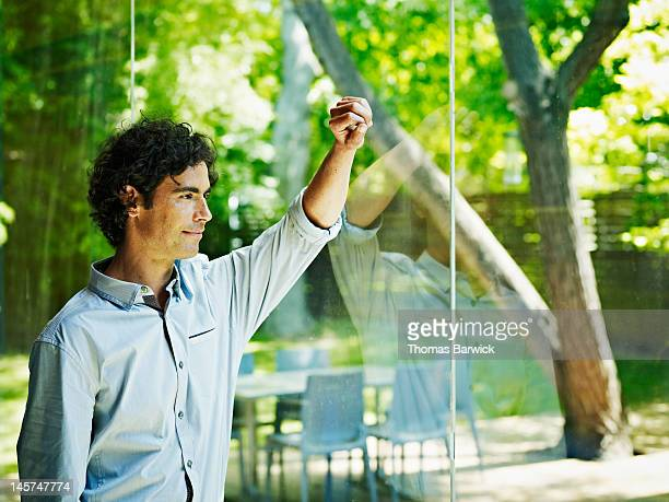 Man standing arm resting against window of home