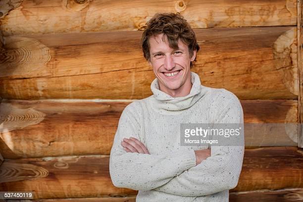 Man standing arms crossed against log cabin
