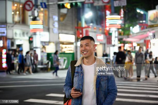 man standing at a cross walk in a busy asian city - incidental people stock pictures, royalty-free photos & images