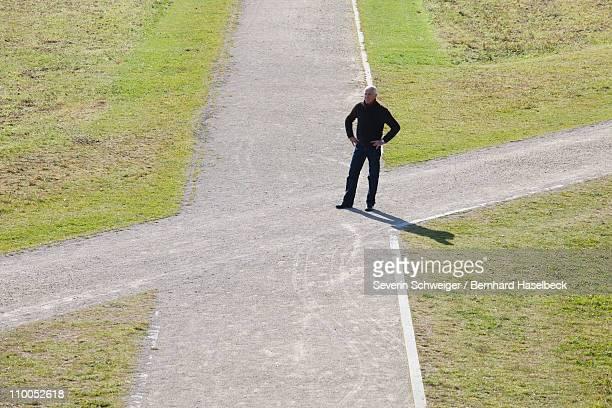 Man standing at a crossroads