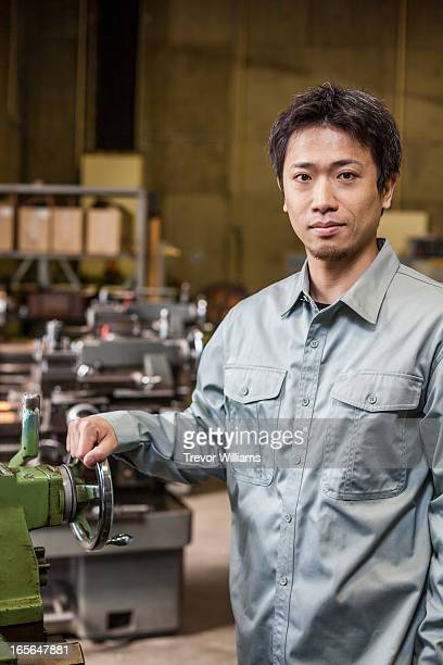 A man standing at a lathe