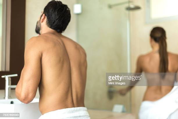 a man standing at a sink in a bathroom, with a woman stepping into a shower. - pareja ducha fotografías e imágenes de stock