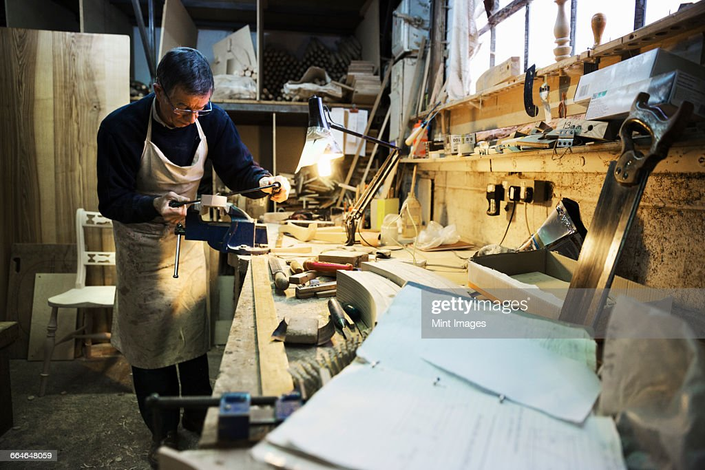 Magnificent Man Standing At A Work Bench In A Carpentry Workshop Working Machost Co Dining Chair Design Ideas Machostcouk