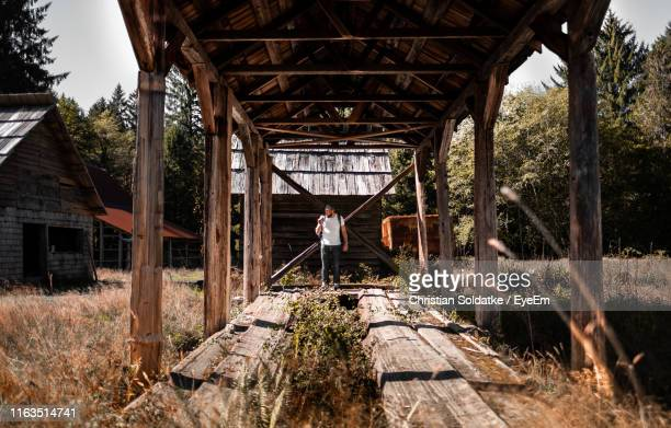 man standing at abandoned hut - christian soldatke stock pictures, royalty-free photos & images